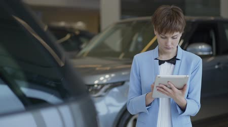 продавщица : Portrait of confident pretty woman in formal wear using her tablet checking cars in motor show. Lady examining vehicles. Professional saleswoman works in car shop Стоковые видеозаписи