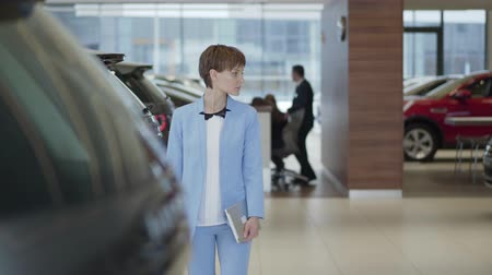 prawo jazdy : Young pretty woman with tablet in hands in formal wear blue suit walking between rows of new cars in motor show choosing one to buy. Concept of buying automobile, auto business