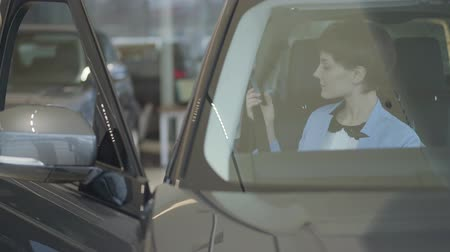 examinar : Young pretty woman in formal wear blue suit wear seat belt sitting inside car in motor show. Modern girl choosing automobile to buy, examining it meticulously. Concept of auto vehicle buying Stock Footage
