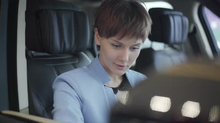 prawo jazdy : Portrait of smiling satisfied pretty woman in formal wear blue suit sitting inside car in front passenger seat. Modern girl choosing automobile to buy, examining it. Camera moves left Wideo