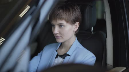 sprzedawca : Confident woman with short hair in classic blue formal suit sitting in the car close up. Modern woman choosing automobile in motor show. Concept of buying a vehicle. Camera moves right