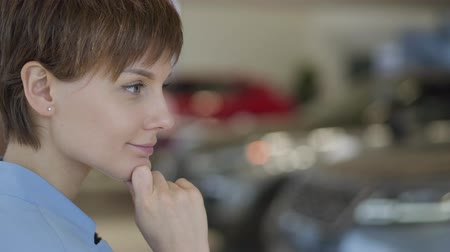 prawo jazdy : Profile of a young woman with short haircut thinking about buying a car in motor show close up. Row of blurred cars are in background. Concept of choosing automobile, auto business Wideo