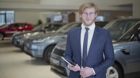 sobre : Portrait of professional salesman with tablet in suit. Picture of bearded man in glasses telling information about cars looking in camera in modern motor show