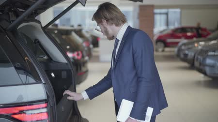 formální : Bearded businessman choosing the car in motor show close up. Tall man holding tablet looks in opened trank and examines vehicle. Serious man choosing automobile in motor show. Concept of buying car