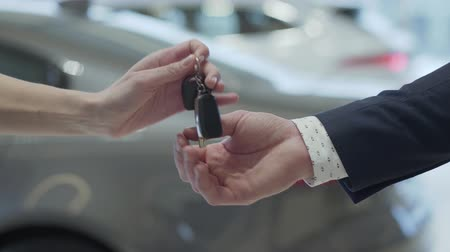 sala de exposição : Male hand gives a car keys to famale hand in the car dealership close up. Unrecognized auto seller and a woman who bought a vehicle shake hands.