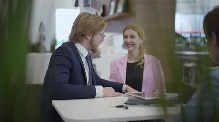 продавщица : Elegant man and woman in formal suits sitting at the table buying new car in modern motor show. Saleswoman gives key to man. Lady is excited, she hugs husband. Businessman buying vehicle for wife