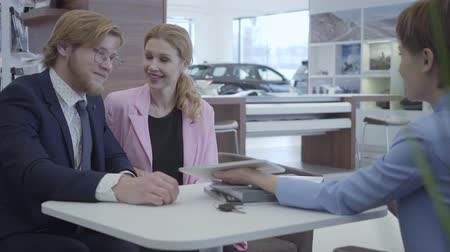 car rental : Car dealer in a stylish suit shows information about their new car on the tablet to young successful couple. Car dealership.