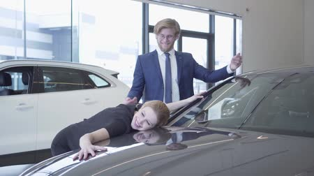 ショールーム : Man and woman in formal wear just bought car in modern motor show. Lady is excited and happy, she hugs automobile, smiling. Businessman buying vehicle for wife 動画素材