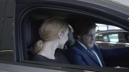 compartimento : Cheerful successful couple sitting in passenger compartment of the new vehicle inspects the interior of the newly purchased auto from the dealership. Car showroom. Stock Footage