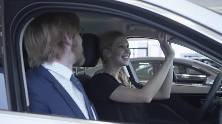 аренда : Happy successful couple sitting in passenger compartment of the new vehicle inspects the interior of the newly purchased auto from the dealership. Car showroom. Стоковые видеозаписи