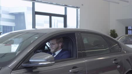 compartimento : Handsome bearded businessman in glasses and business suit in passenger compartment of the new car. Car dealership.