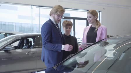 vendedor : Bearded salesman in a business suit tells two successful young girls information about a new auto at a car dealership. Car showroom.