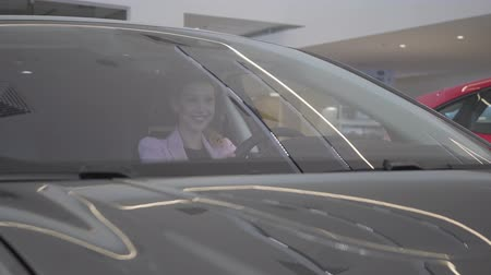 car rental : Happy cute young girl in passenger compartment of the new car. The girl is calling for a car manager. Car dealership.