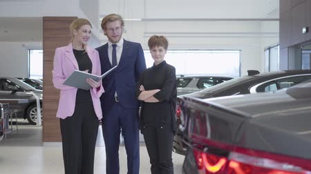 prestigious : Car saleswoman shows a young couple information about luxury car in expensive car showroom. Successful couple buys a new auto at a prestigious car dealership.