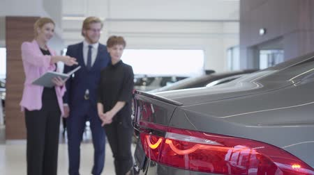 prestigious : Car saleswoman shows a young couple their new car. A successful couple buys a new auto at a prestigious car dealership. Stock Footage
