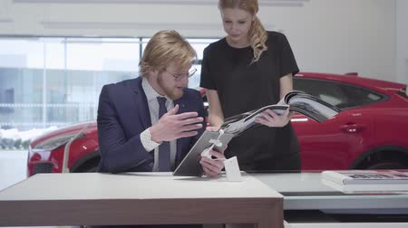 catalog : Successful business woman scrolls through the catalog with vehicles standing near a stylish salesman in a business suit who sits at a table in a car dealership. Motor car. Stock Footage