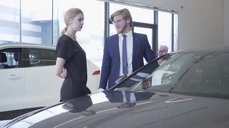 販売員 : Smiling bearded salesman in business suit showing new auto to successful business woman at car dealership. Showroom