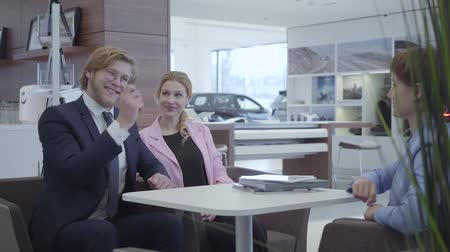 продавщица : Saleswoman in a stylish suit transmitting the keys to the new car happy successful business couple. A joyful bearded guy in business suit happily picks up the keys of his new vehicle. Car showroom