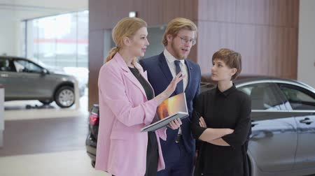 vendedora : Salesswoman in pink jacket showing information in book to customers. Professional saleswoman helps man and woman to choose vehicle. Concept of buying automobile, auto business Stock Footage