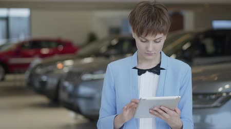examinar : Portrait confident cute woman in formal wear using her tablet stands in front of blurred cars in motor show. Professional saleswoman works in car dealership