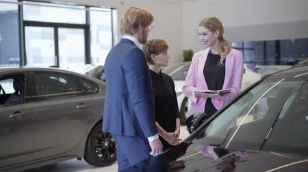 catalog : A confident beautiful woman seller holding a catalog with cars and their characteristics provides a young successful business couple with information about a new vehicle. Car dealership. Stock Footage