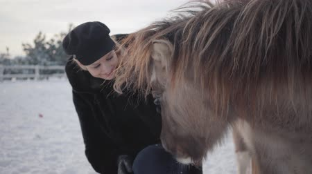 冬 : Young smiling woman strokes muzzle of adorable small pony at a ranch close up. Girl in warm clothing spends time with horse in the winter paddock. Concept of horse breeding