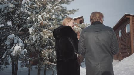 hekje : Man and woman in warm coats walking in snow yard near wooden houses toward male figure with white horse. Young family rests outdoors in winter Stockvideo