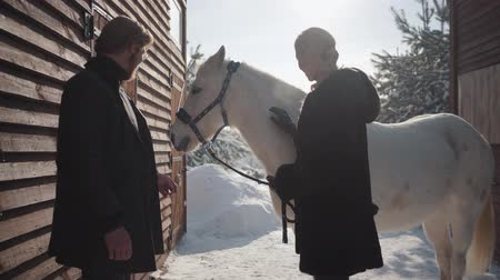 dizgin : Blond woman and tall man standing with white horse at the snow winter ranch. Girl strokes animal. Happy couple spend time outdoors at farm.