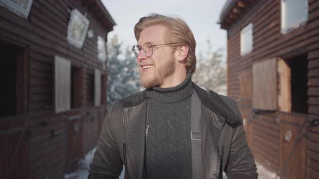 dacha : Portrait of a handsome bearded guy with glasses dressed in a warm sweater and wide-open jacket. Guy smiles, pulls up suspenders and looks around.