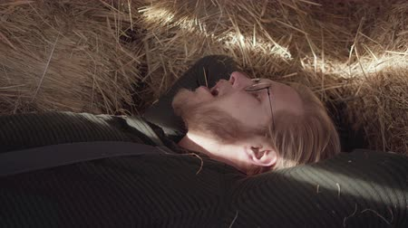 descuidado : Portrait of bearded man in glasses with laying in the hay with a straw in the mouth close up. Young thoughtful farmer resting after working day