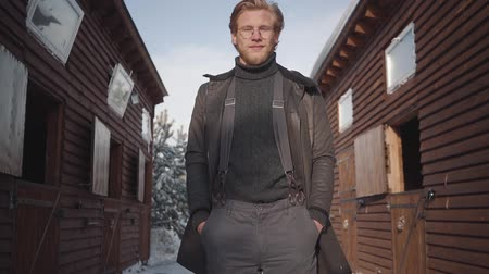 dacha : Confident bearded man in glasses standing between two wooden houses with hands in pockets. Young farmer in coat and pants with suspenders looking in camera. Shooting from the bottom, zooming closer Stock Footage