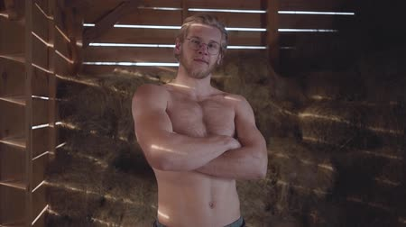 usual : Portrait of a handsome bearded guy in glasses with a bare torso standing in the barn on the background of hay. Slow motion. Stock Footage