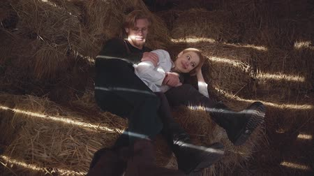 mentiras : A young couple lies hugging hay in the barn. Happy smiling boy and girl spend time together. Slow motion.