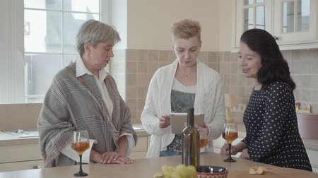 meia idade : Woman showing to her friends photos on tablet. Group of three middle aged women communicating spending time in the kitchen at home with wine and fruits. Modern grandmothers having fun. Slow motion