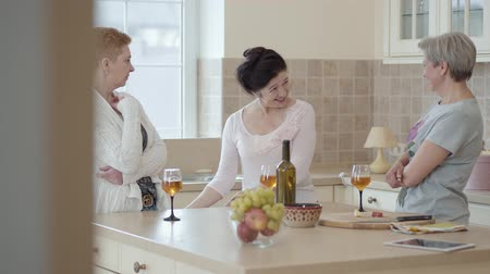 gesticulando : Three mature women communicating at home standing near modern table in the kitchen. Lady telling story emotionaly, actively gesticulating. Senior ladies having fun drinking wine. Camera moves right