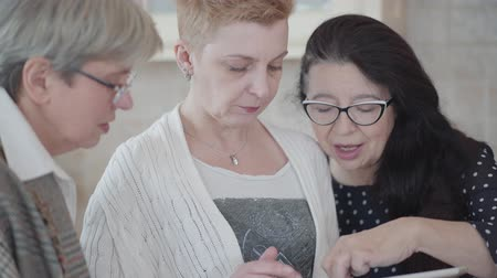 middle age : Portrait three mature girlfriends watching something interesting on the tablet and are actively discussing. Adult women make online shopping choosing clothes or accessories for good discounts. Stock Footage