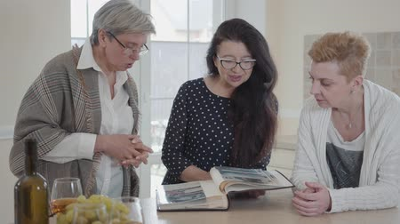 photo album : Senior woman with long black hair showing to friends her old photo album. Group of three middle aged mature women communicating chatting in modern kitchen at home
