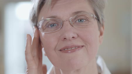 vráska : Portrait of a mature white-haired woman wearing glasses and looking at the camera close up. Dostupné videozáznamy