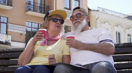 két ember : Portrait of stylish old people drink coffee and relaxing on the bench in the city