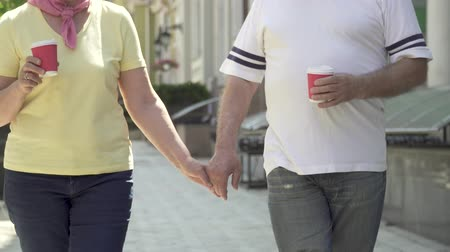 recreational park : Senior couple walking in the city holding hands and coffee