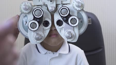 phoropter : Optometrist examining male patient on phoropter in ophthalmology clinic. African American boy doing eye test. Slow motion. Stock Footage