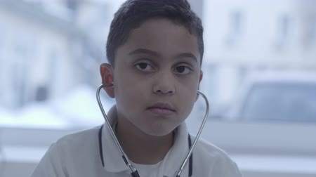 hypertension : Portrait of cute funny thoughtful small boy with stethoscope in his ears looking around. Healthcare, healthy lifestyle and medical service concept