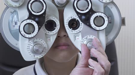 pediatria : Little boys eye examination at optometrist ophthalmologist using phoropter close up. Hands of doctor in white medical coat puts phoropter to eyes of teen African American boy Wideo