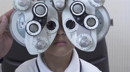 tıbbi bakım : Little boys eye examination at optometrist ophthalmologist using phoropter close up. Hand of the doctor changing glass on one eye of teen boy on phoropter. Camera moves closer Stok Video