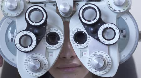 phoropter : Young woman eyes examination at optometrist ophthalmologist using phoropter close up. Cute woman smiles looking through glass of optometry machine. Hand of the doctor changing glass. Slow motion Stock Footage