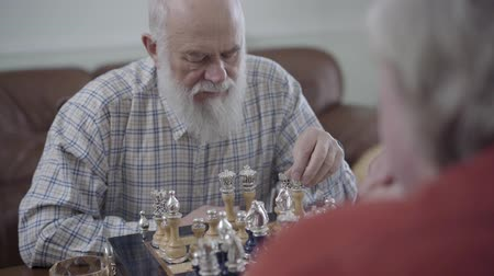 opponent : Two old friends playing chess sitting at home on the leather sofa. Bearded man thinking which chess piece to make a move. Caucasian old men neighbors playing chess joyfully indoors Stock Footage