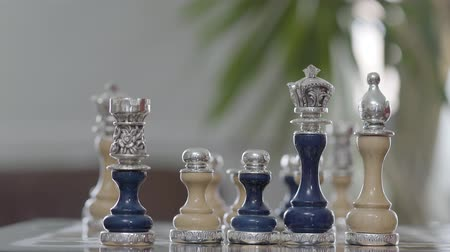 королева : The beautiful chess set with silver inserts standing on chess board close up. Chess board game, business competitive concept. Intelligence challenge and business competition success play Стоковые видеозаписи