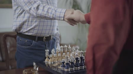 porażka : Two men shaking hands over a chess board before start game and sit at the small table. The beautiful chess set with silver inserts standing on chess board. Mature senior men playing intelligence game