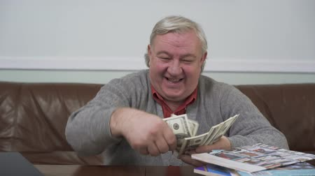 atmak : Happy old man throwing away the dollars sitting at the wooden table close up. Positive rich man demonstrates his money. Funny grandfather relaxing at home sitting on the leather sofa. Leisure of prosperous retired man Stok Video
