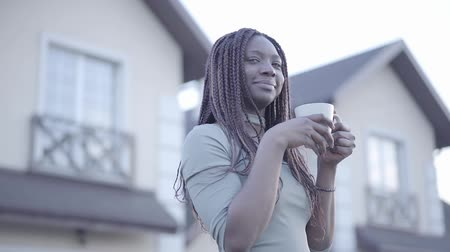 косички : Portrait of pretty confident african american young black smiling woman with hot cup of coffee on the street. Slow motion